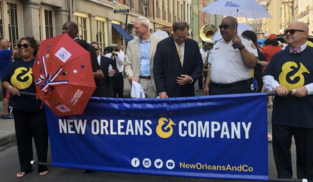 people in french quarter new orleans holding a new orleans and company sign
