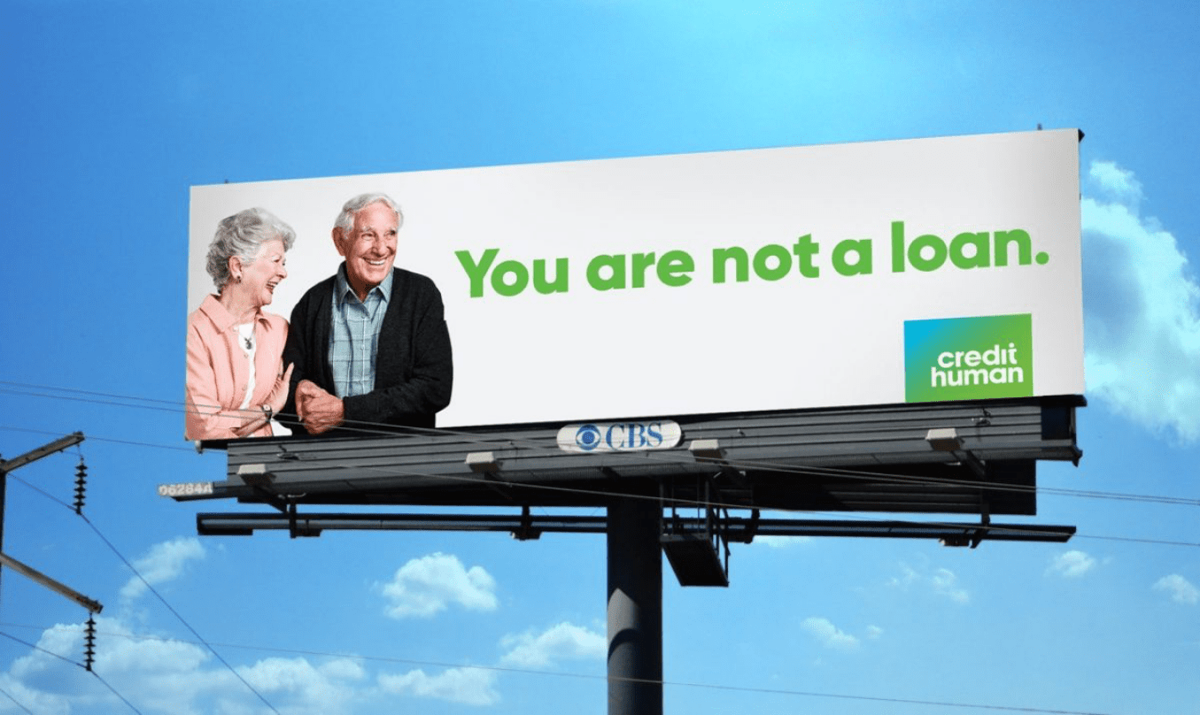 elterly couple holding hands and locking arms while smiling on a billboard supporting loans from credit human