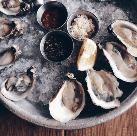 fresh oysters and sauce on a bed of ice