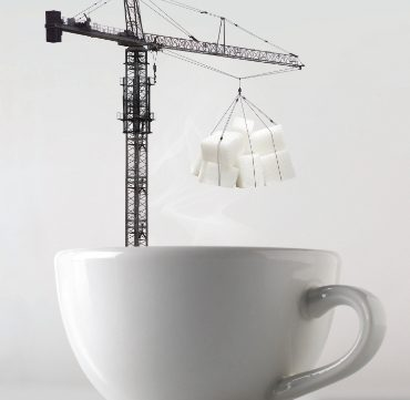 crane lowering sugar cubes into a cup of hot coffee